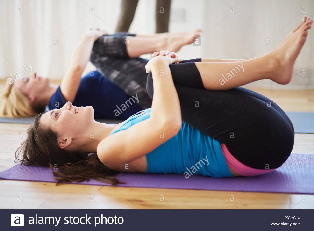 Studenti di sesso femminile che giace sul retro abbracciando le ginocchia in classe di pilates Immagini Stock