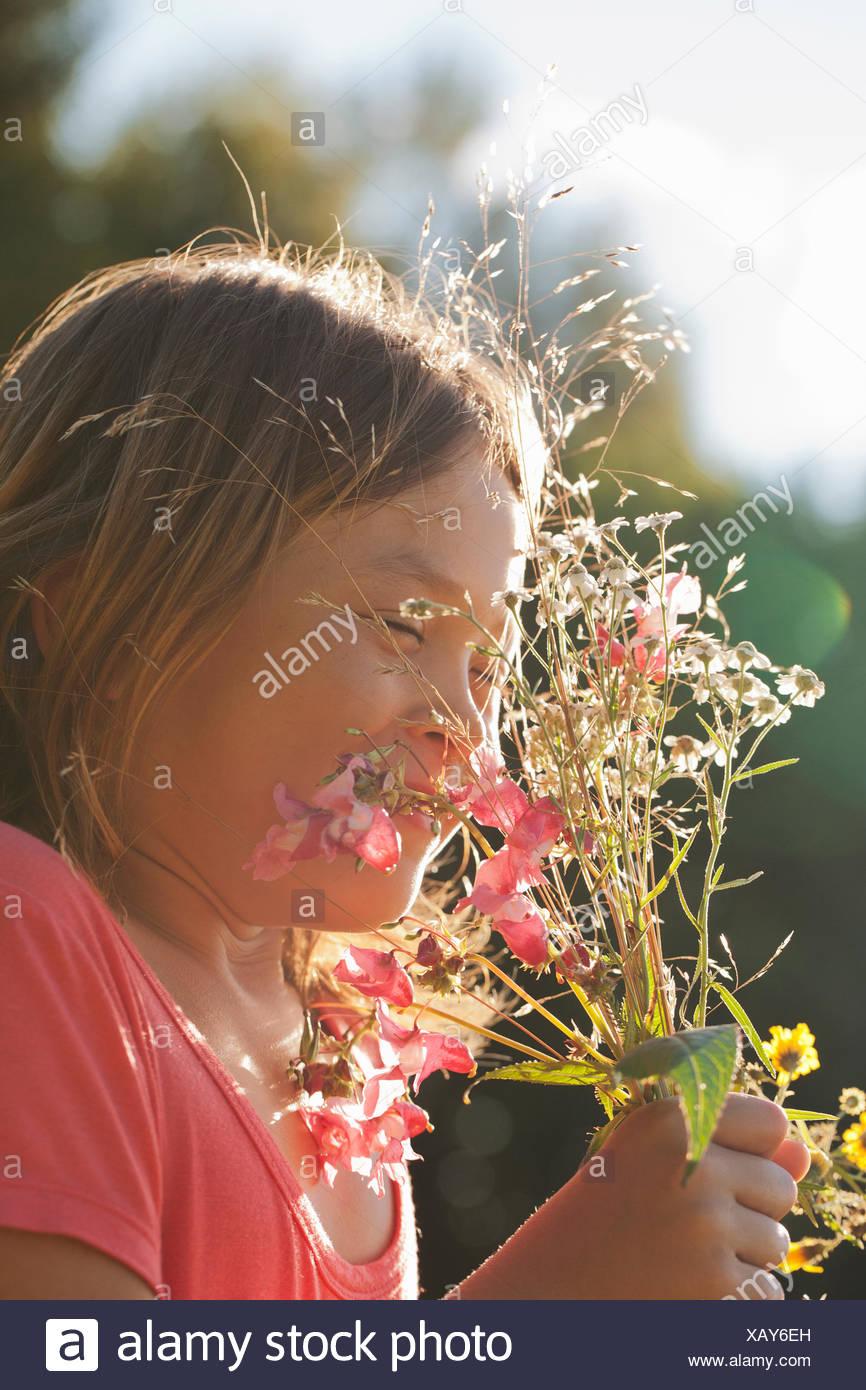La ragazza (10-11) azienda mazzetto di fiori selvatici Immagini Stock