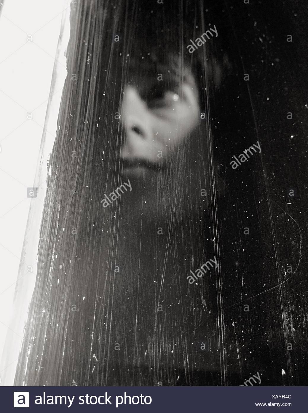 Donna che guarda fuori la finestra Foto Stock