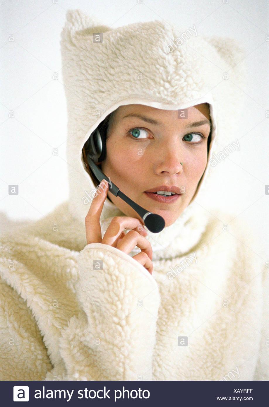 Donna che indossa lanosa felpa con cappuccio, utilizzando la cuffia Immagini Stock