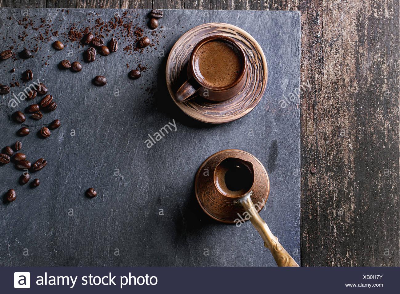Ceramica marrone tazza di caffè, rame antico cezve e i chicchi di caffè. Oltre nero ardesia come sfondo. Con copia spazio al centro. Top v Immagini Stock