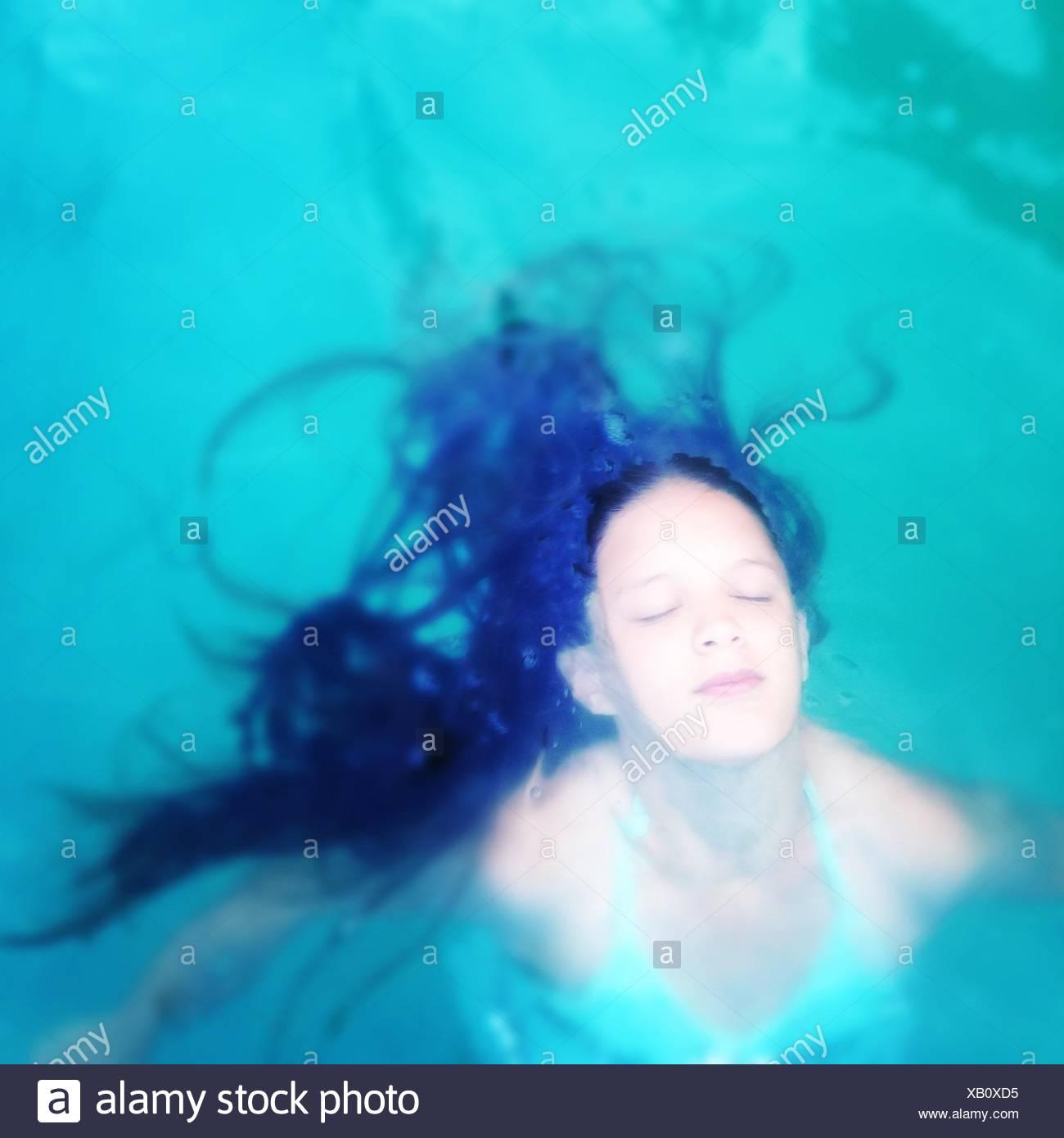 Angolo di Alta Vista della giovane donna con gli occhi chiusi in piscina Immagini Stock