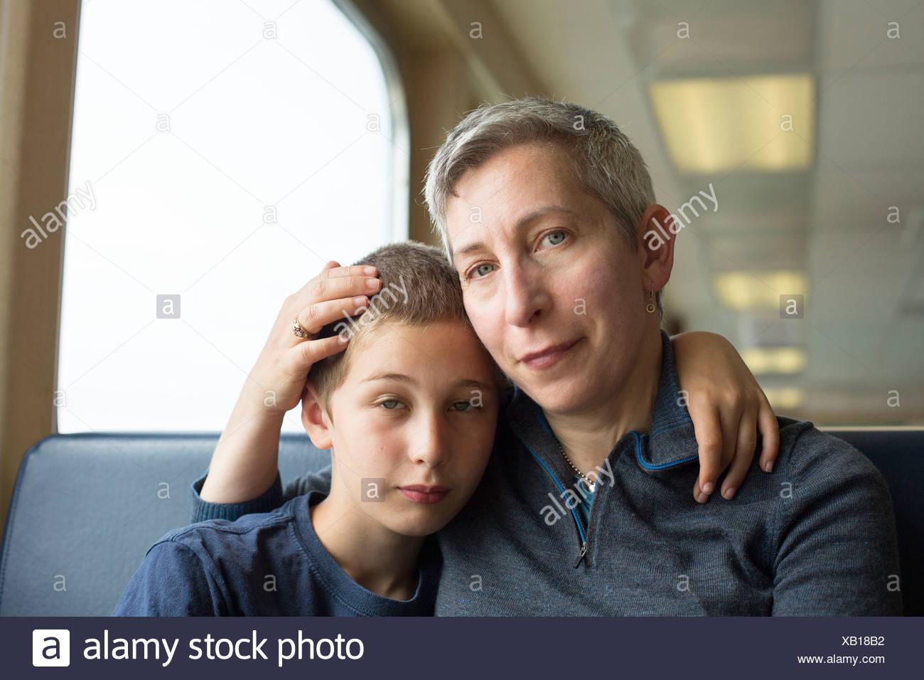 Madre e figlio seduti insieme con il braccio intorno Immagini Stock
