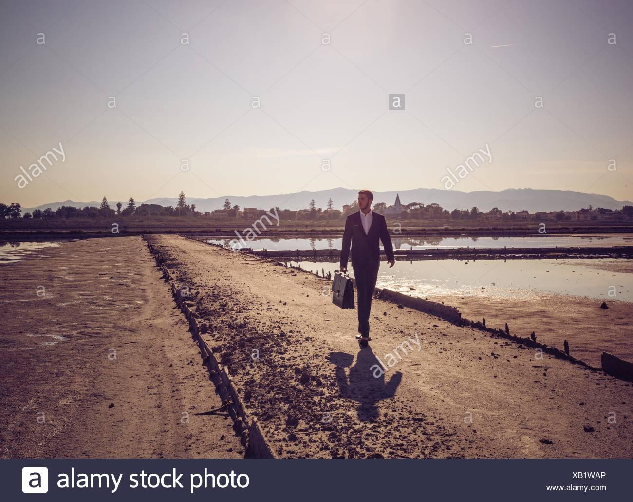 Adulto medio imprenditore valigetta porta camminando lungo la spiaggia Immagini Stock