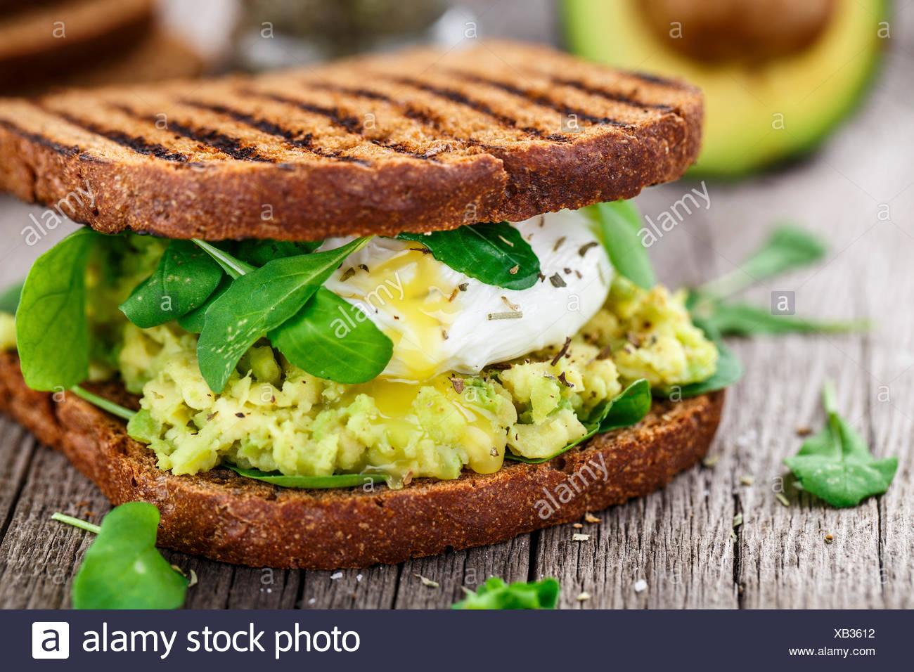 Sandwich alla griglia con avocado, uovo in camicia e rucola sul tavolo di legno Immagini Stock