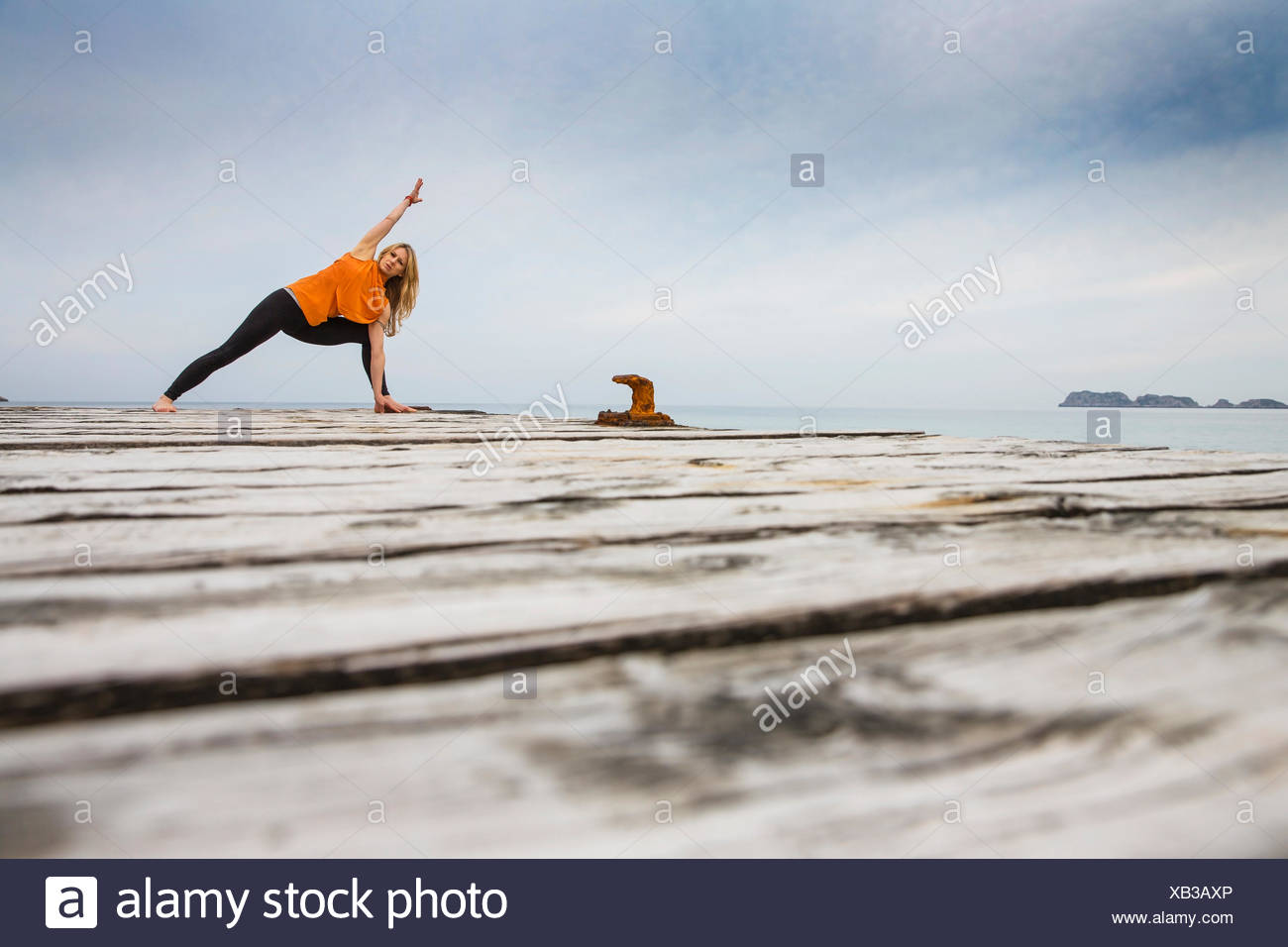 Metà donna adulta a praticare yoga posizione sul mare di legno pier Immagini Stock