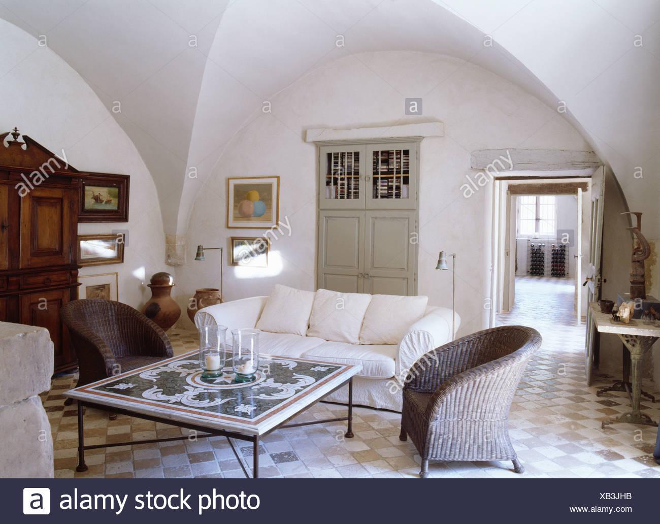 Grigio poltrone in vimini e divano bianco piastrellate intorno a un