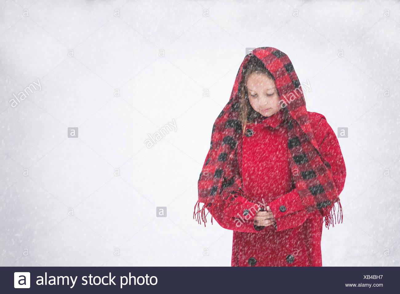 La ragazza (8-9) nel rivestimento di colore rosso in presenza di neve Immagini Stock