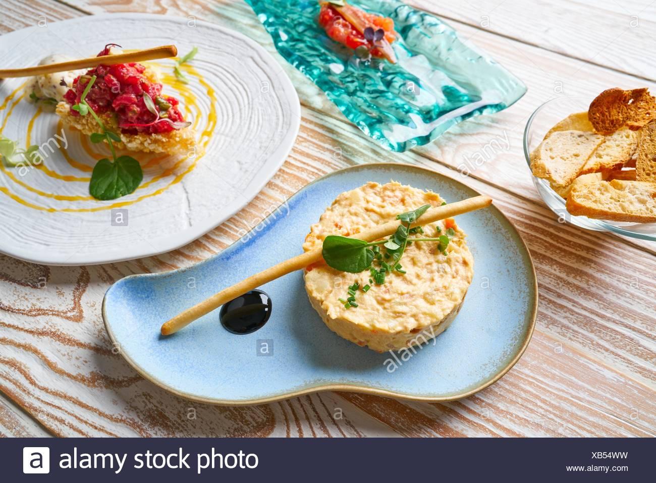 Cibo antipasti insalata di patate tartare di manzo e le acciughe con pomodoro Tapas. Immagini Stock