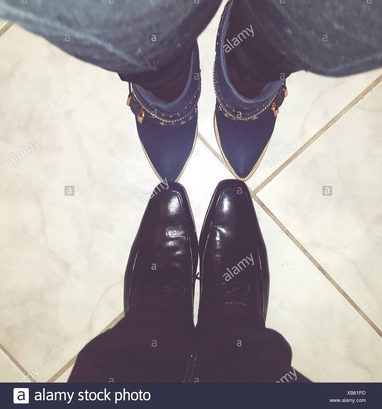 L uomo e la donna le gambe tra loro affacciate Immagini Stock