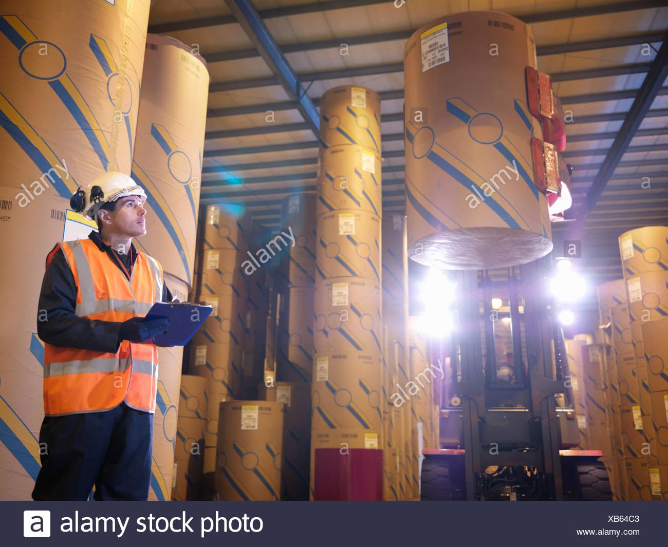 Lavoratore porta con Clip board e il carrello elevatore a forche Immagini Stock