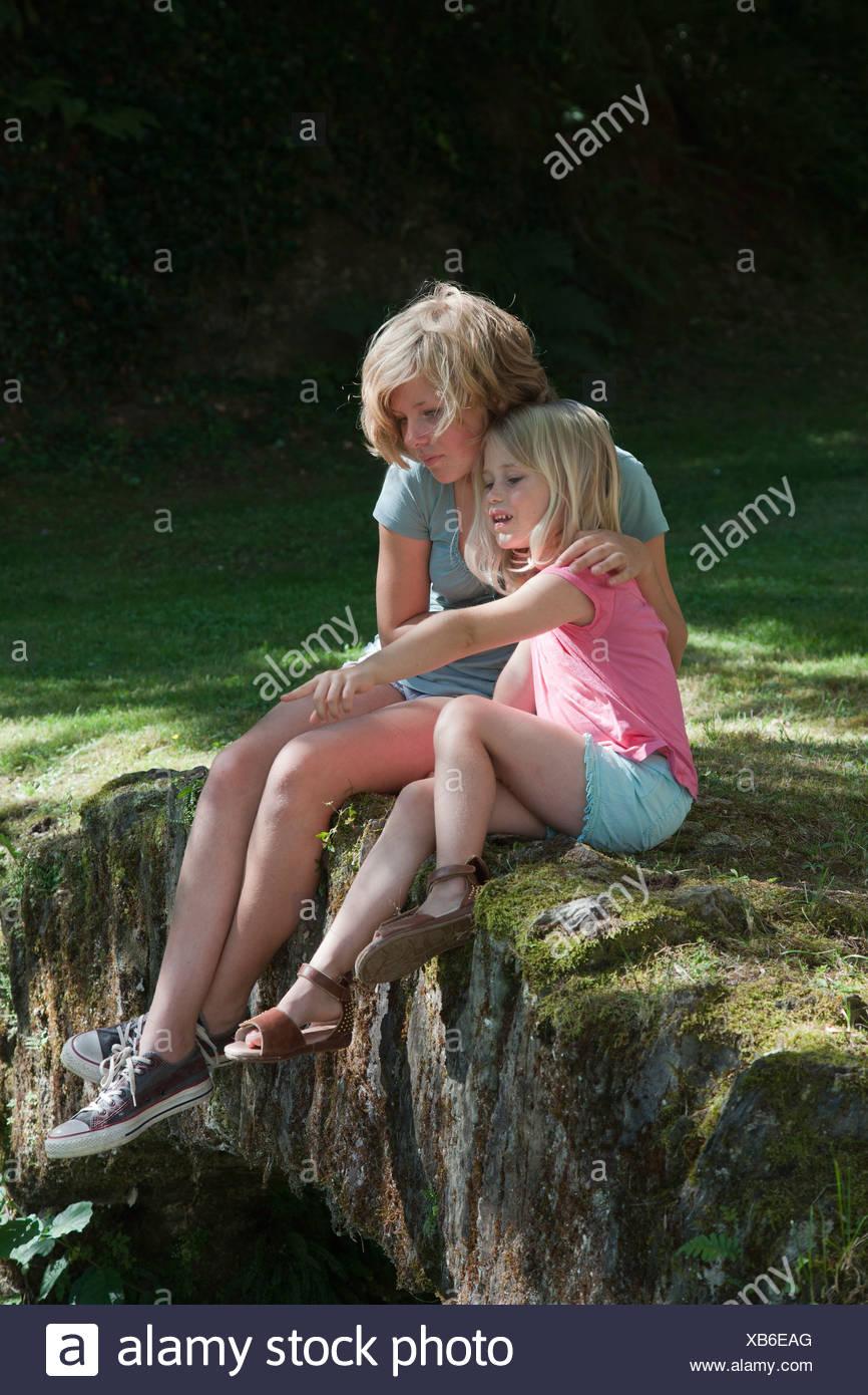 Sorelle seduti in giardino Immagini Stock