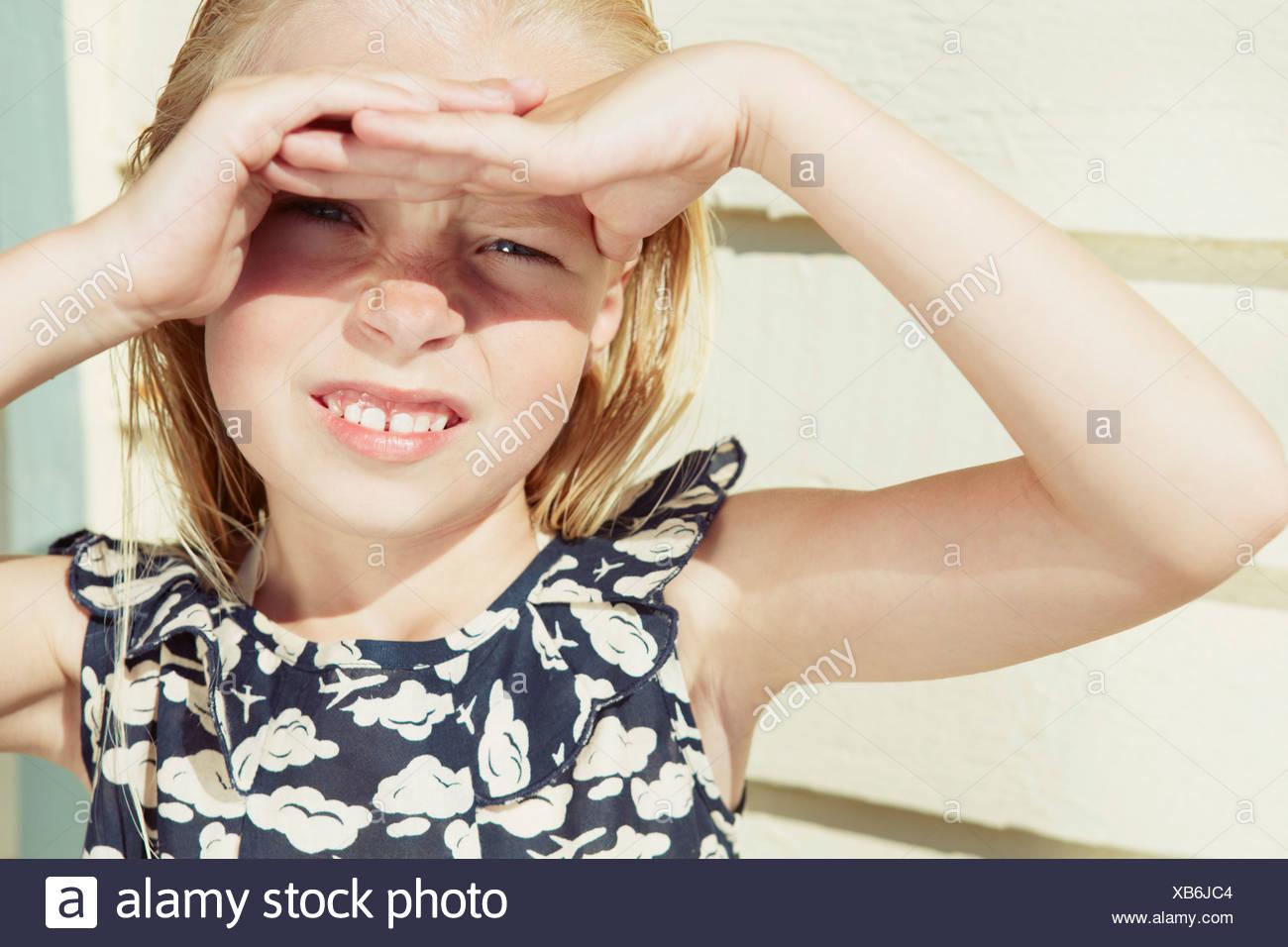 Bambino che copre la sua gli occhi dai riflessi del sole Immagini Stock