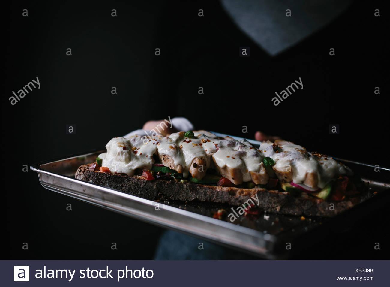 Una donna è in possesso di un pollo caprese aperto di fronte (tartine) sandwich che appena uscito dal forno. Immagini Stock
