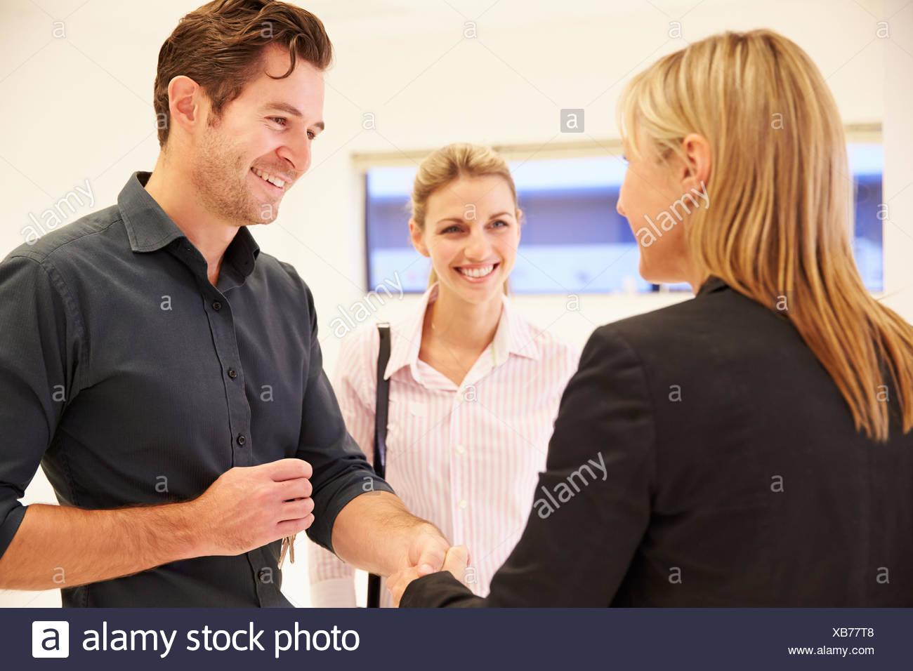Agente immobiliare stringono le mani con i clienti in ufficio vuoto Immagini Stock