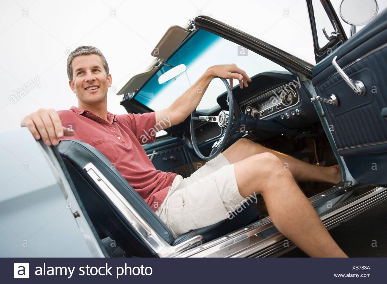 Un uomo sorridente con il sale e il pepe capelli colorati nella sua metà  40 s siede nel suo classico degli anni sessanta era Ford Mustang su un  estate ... d1c7df33110b