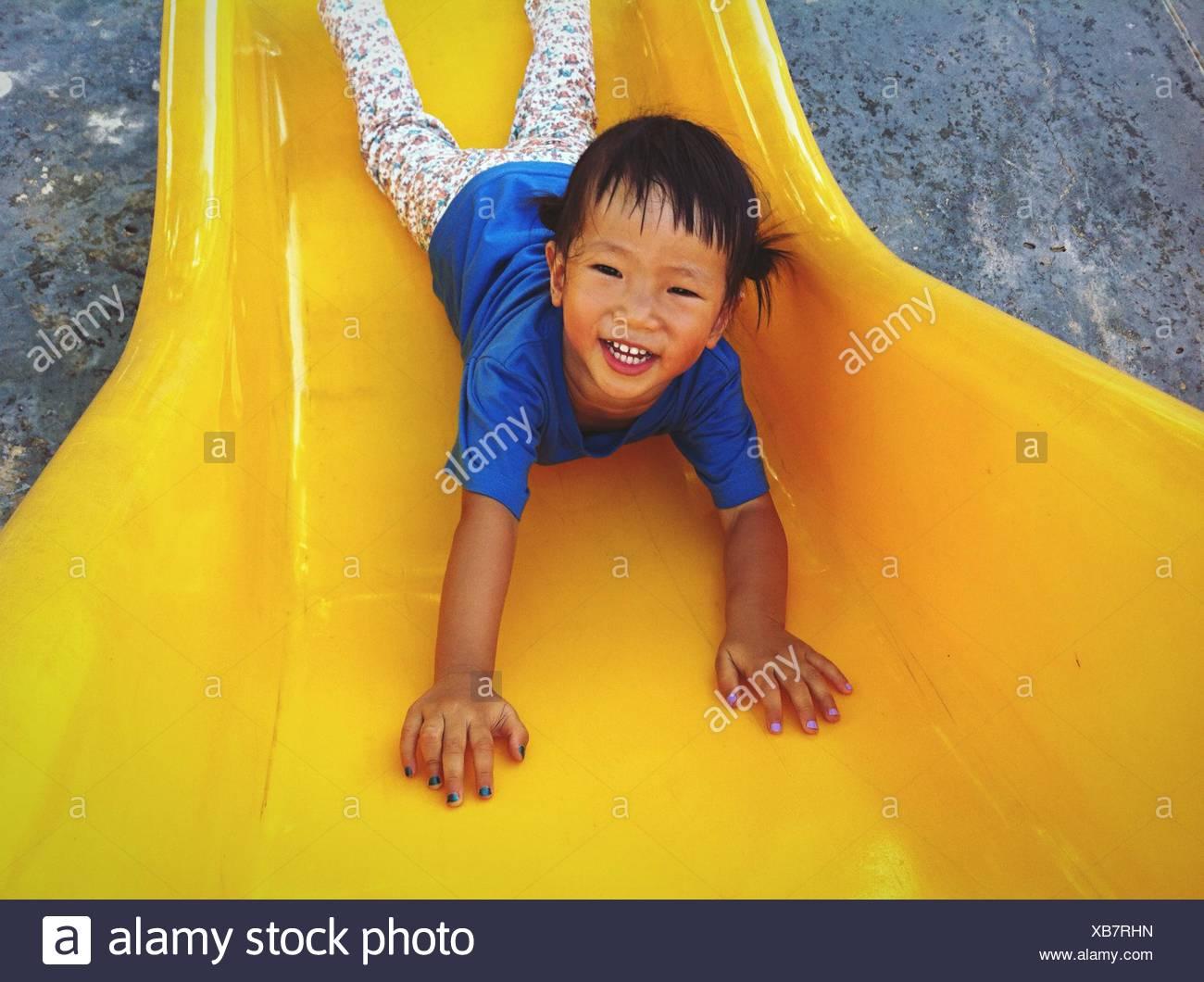 Ritratto di Felice ragazza che gioca sulla slitta di colore giallo nel parco giochi Immagini Stock
