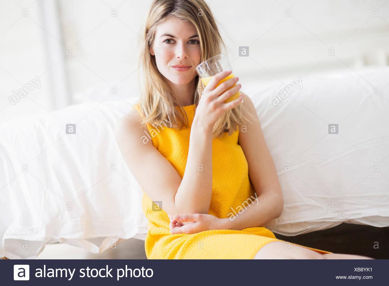 Donna di bere succo di arancia Immagini Stock