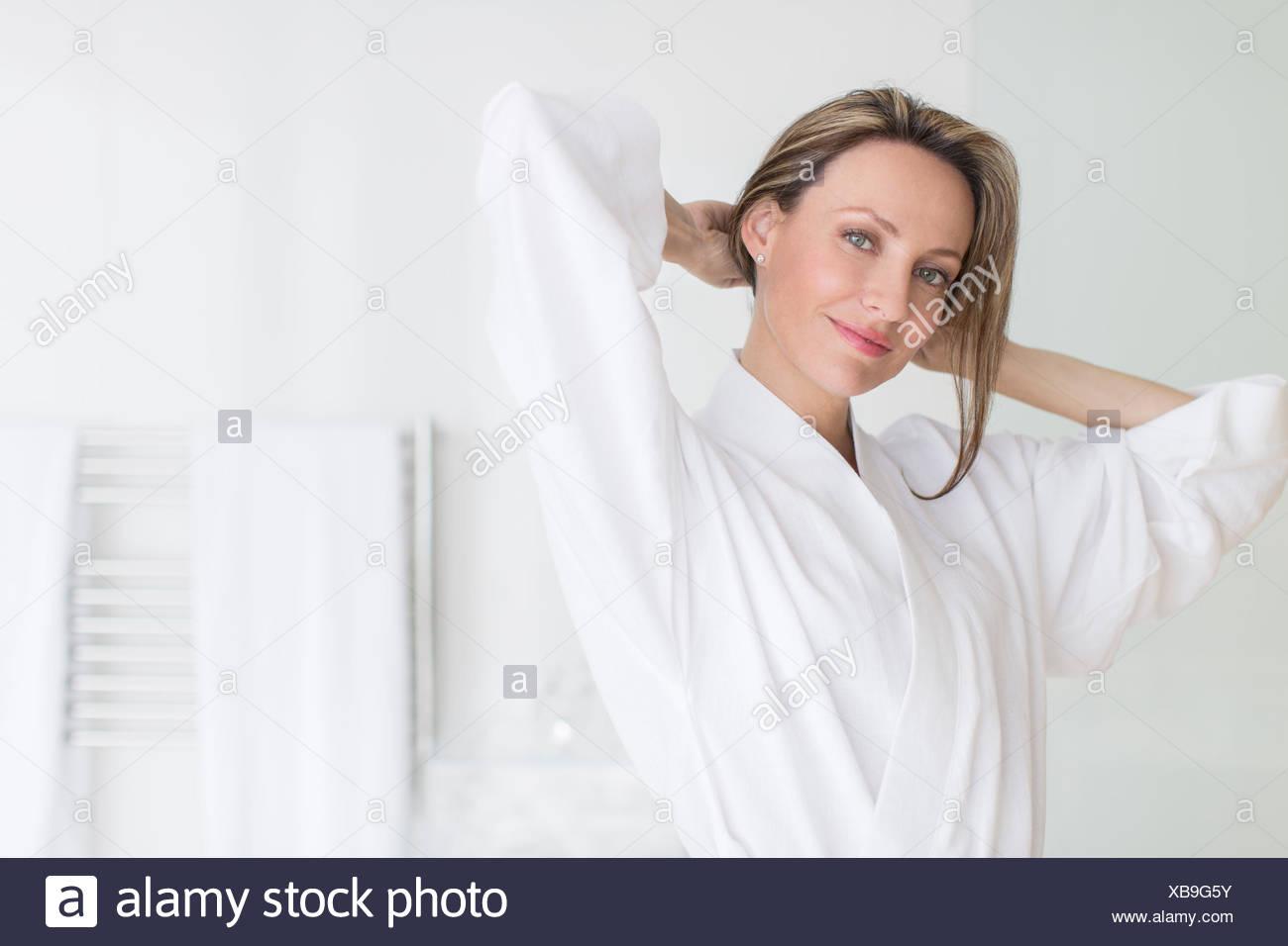 Donna sorridente indossare accappatoio Immagini Stock