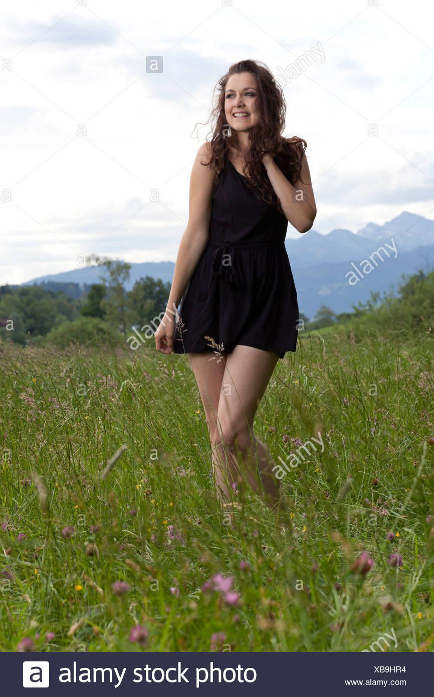 879b933f028a Giovane donna in un corto abito nero in posa l erba lunga Immagini Stock