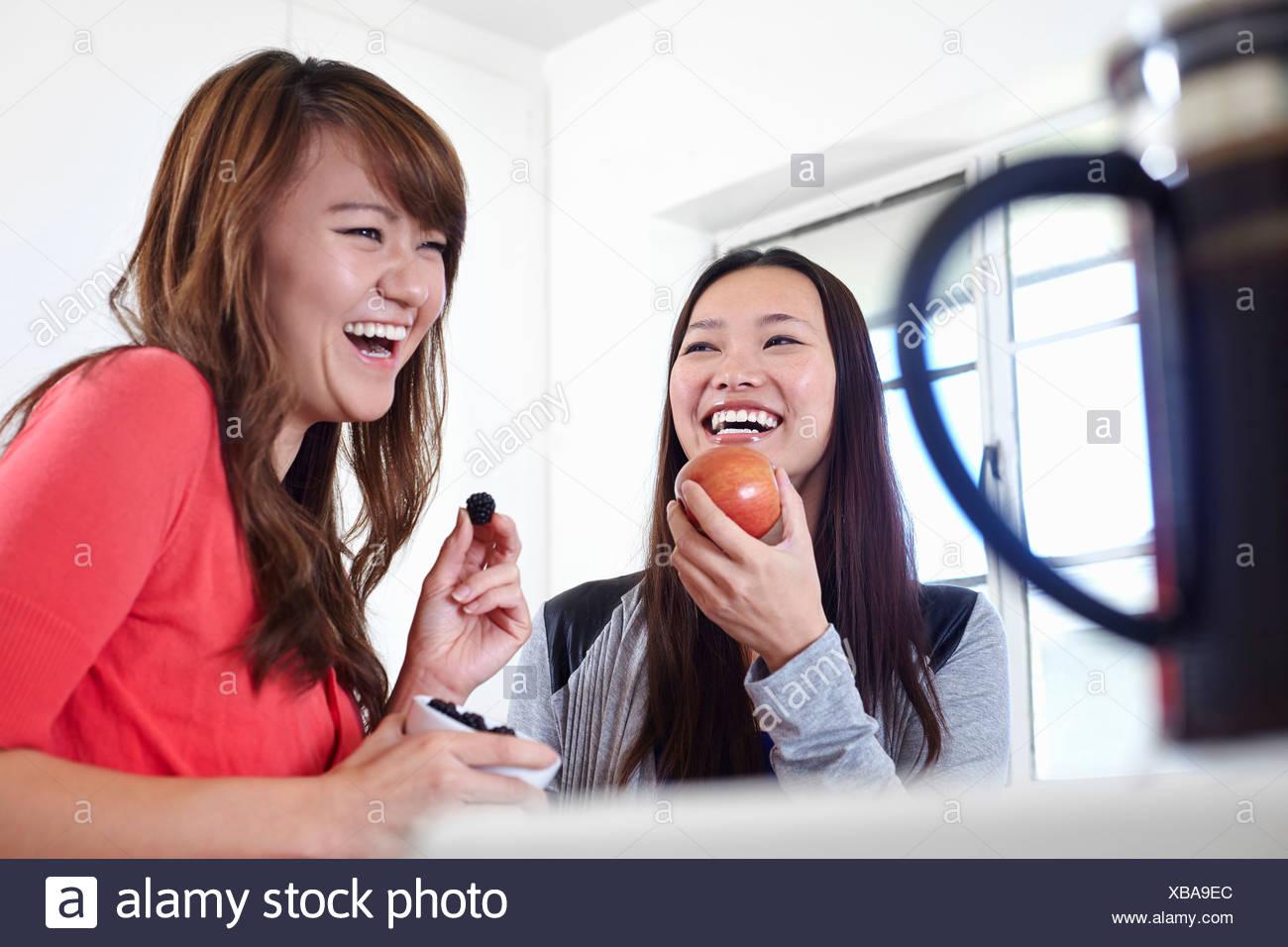 Due giovani donne in cucina mangiare la frutta Immagini Stock