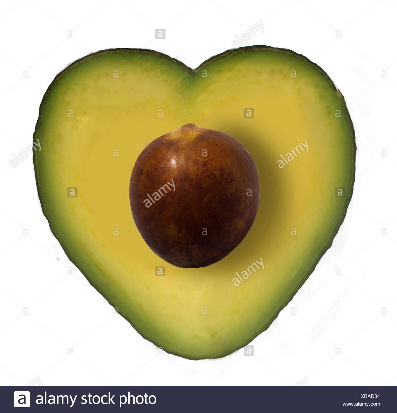 Close-Up di Avocado tagliato a forma di cuore contro uno sfondo bianco Immagini Stock