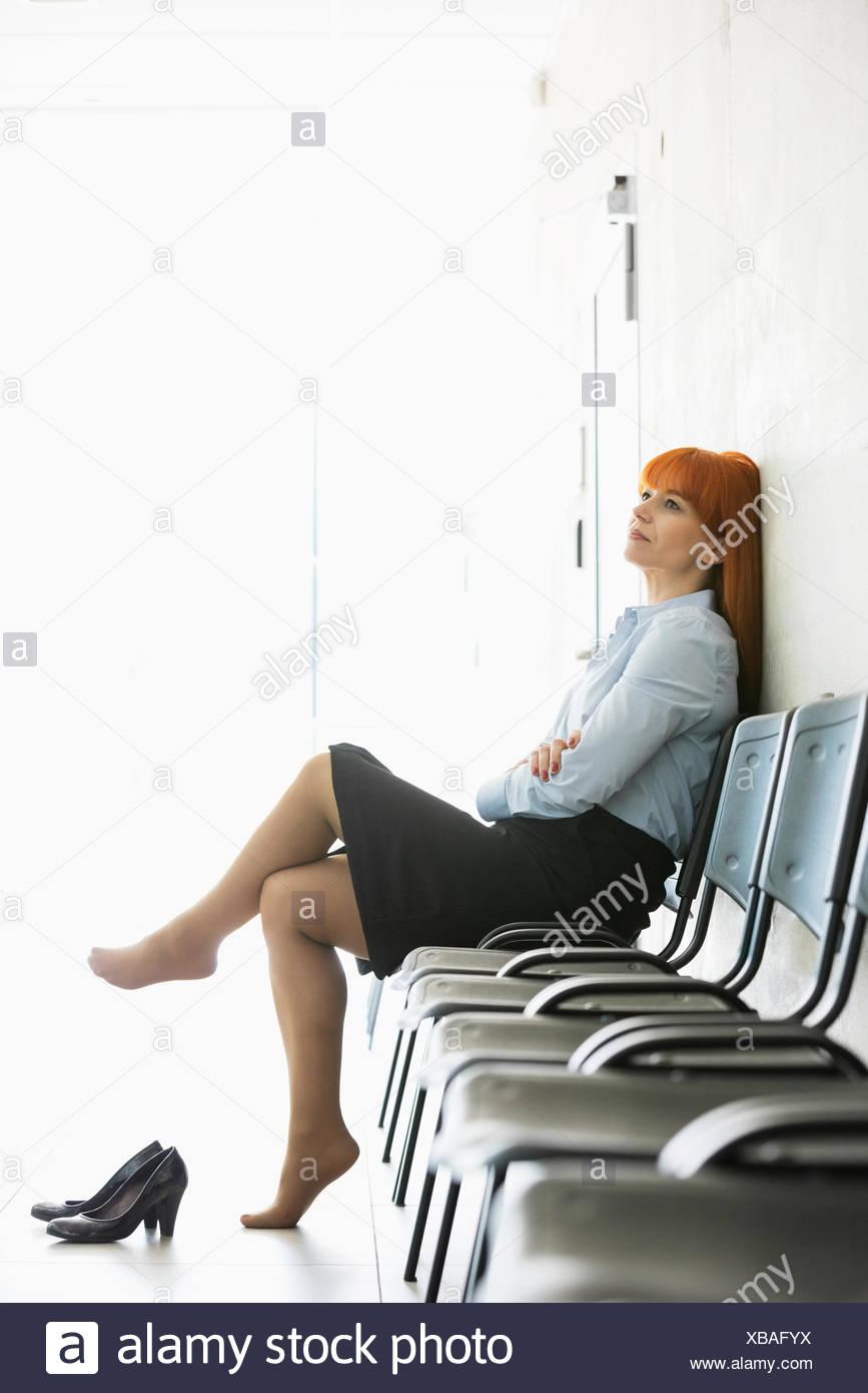 Riflessivo imprenditrice seduta con le gambe incrociate sulla sedia in ufficio Immagini Stock
