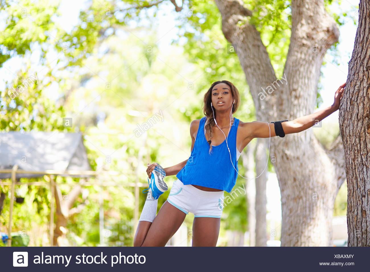 Giovani femmine runner il riscaldamento in posizione di parcheggio Immagini Stock