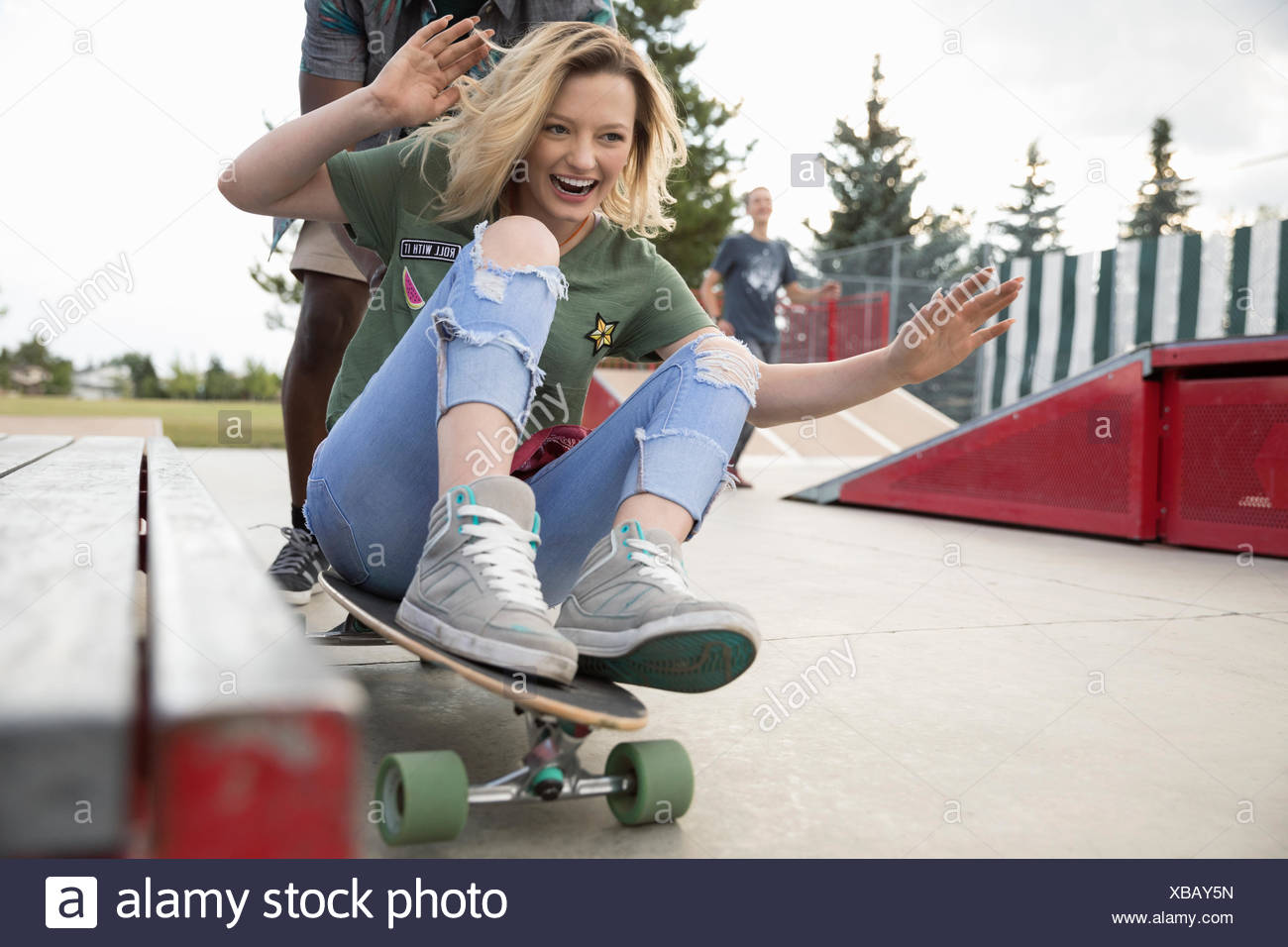 Giocoso ragazza adolescente a cavallo su skateboard a skate park Immagini Stock