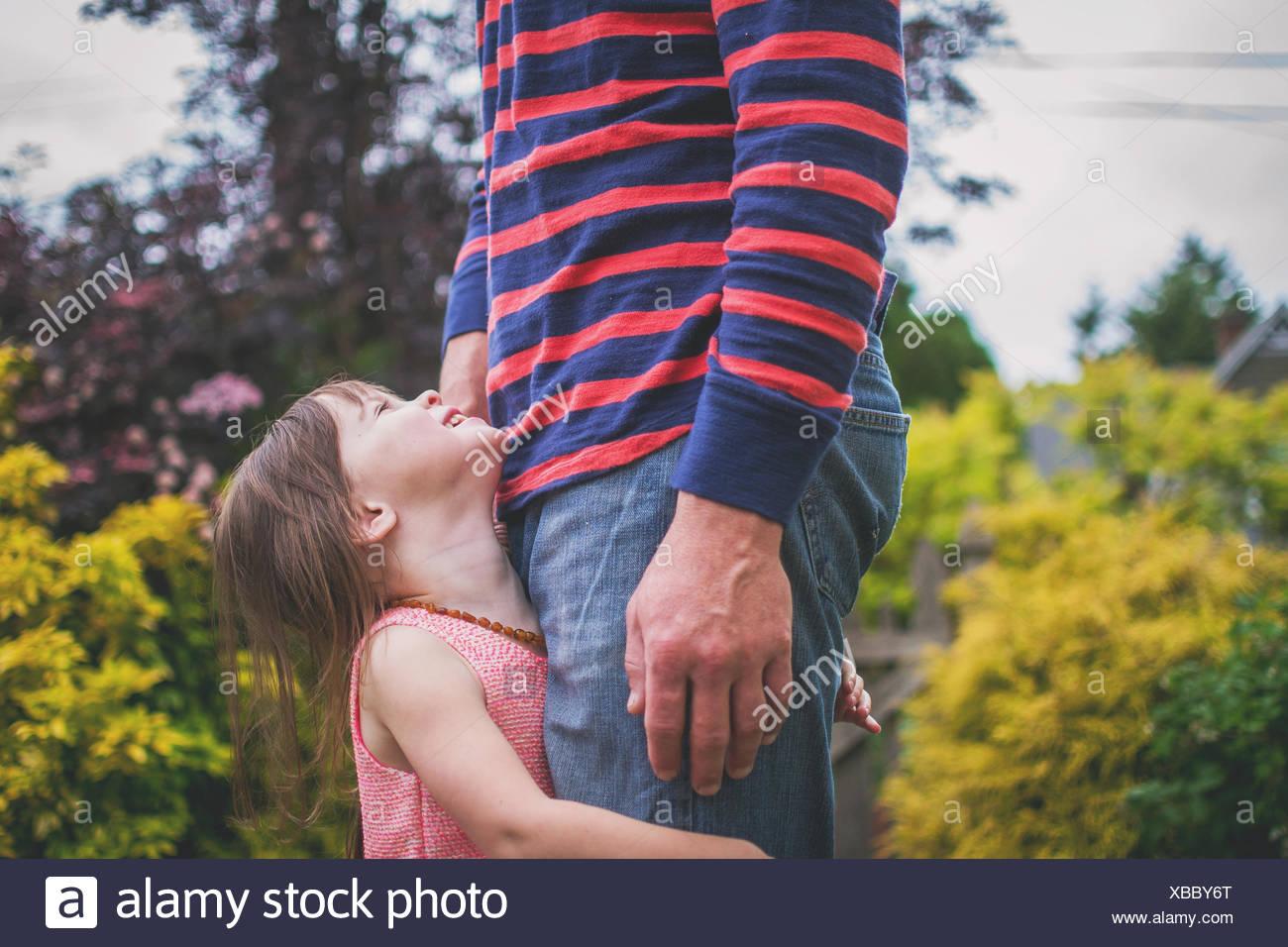 Figlia di padre di contenimento per le gambe, guardando verso l'alto Immagini Stock