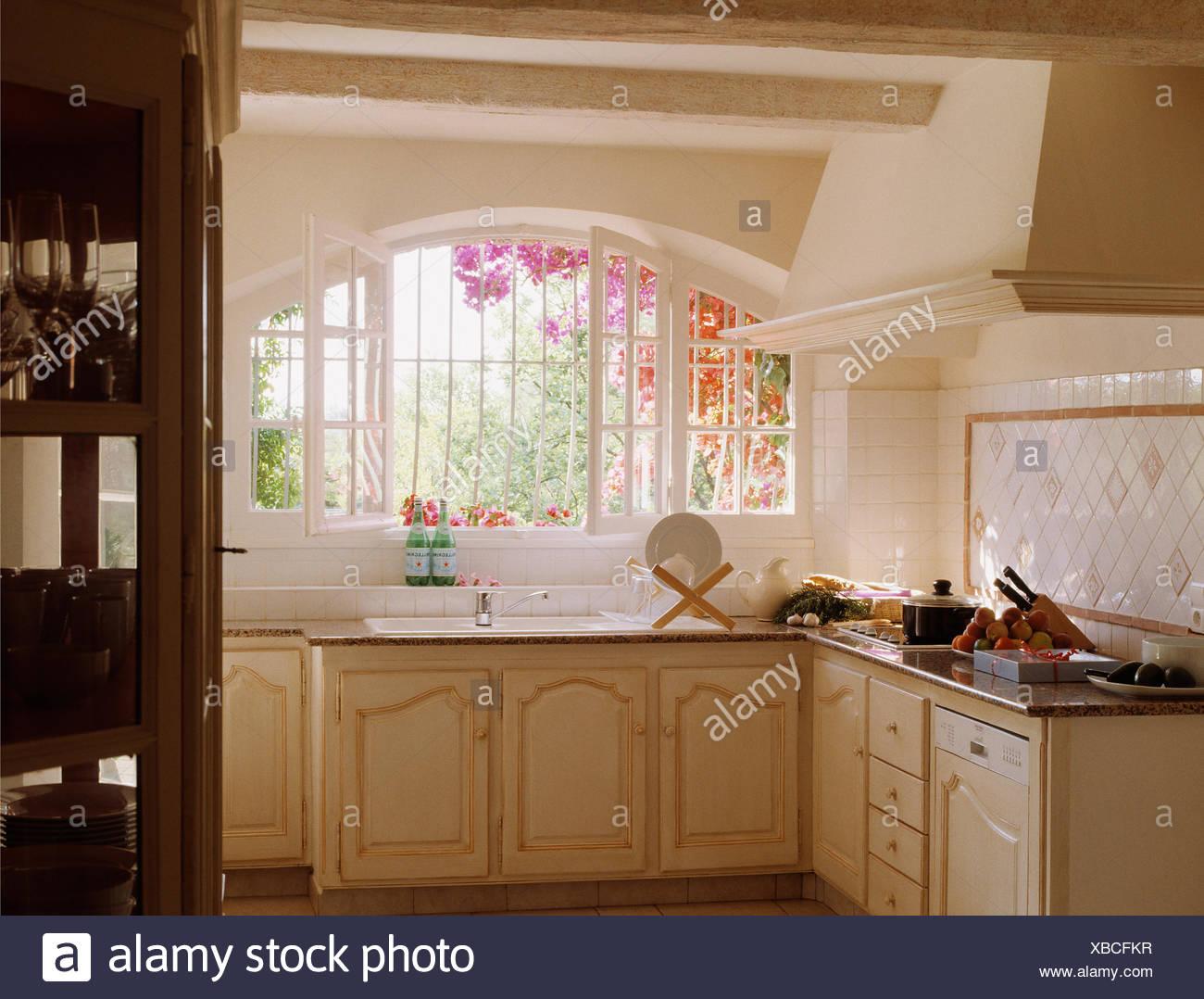 Crema paese francese cucina con lavello sotto la finestra aperta per giardino foto immagine - Cucine sotto finestra ...