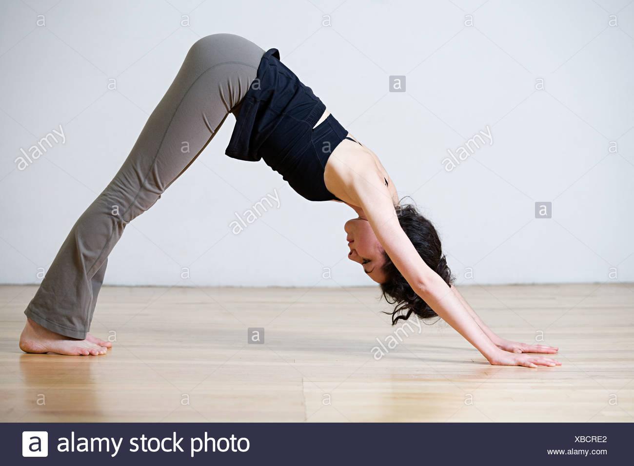 La donna nella posizione del Cane con la testa in giù la posizione durante lo yoga Immagini Stock