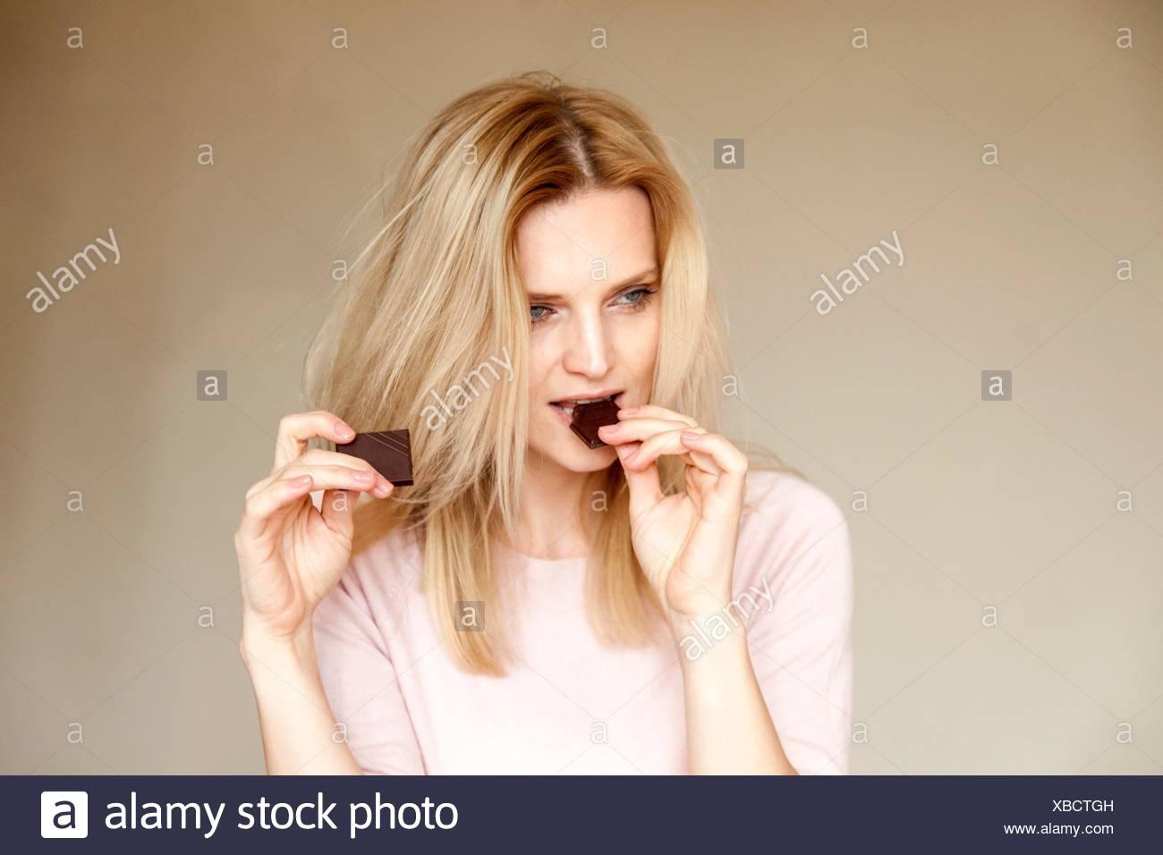 Ritratto di bella donna con capelli lunghi biondi mangiando cioccolato bar Immagini Stock
