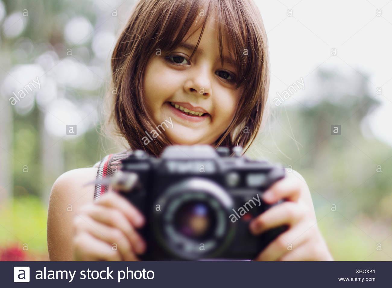 Ritratto di una ragazza sorridente tenere la fotocamera all'aperto Immagini Stock