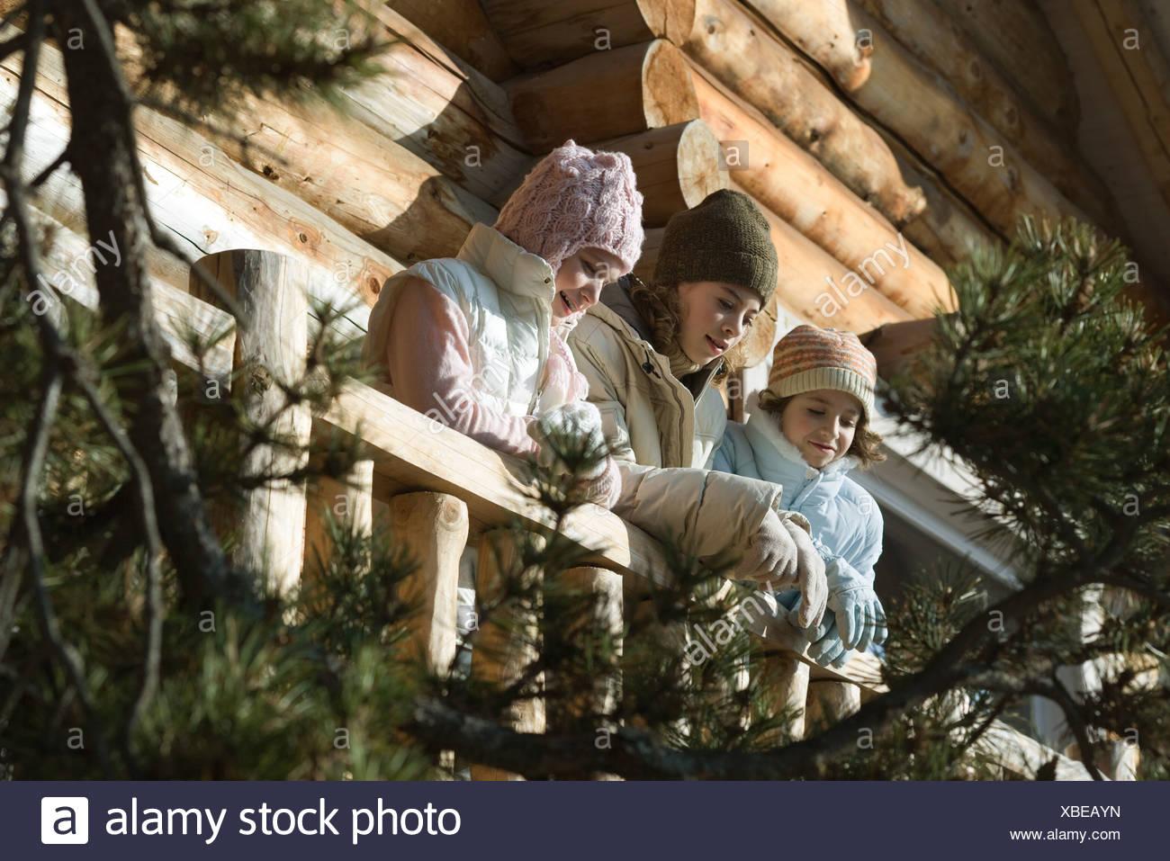 Tre o preteen teen ragazze in piedi sul ponte di log cabin, guardando lontano, a basso angolo di visione Immagini Stock