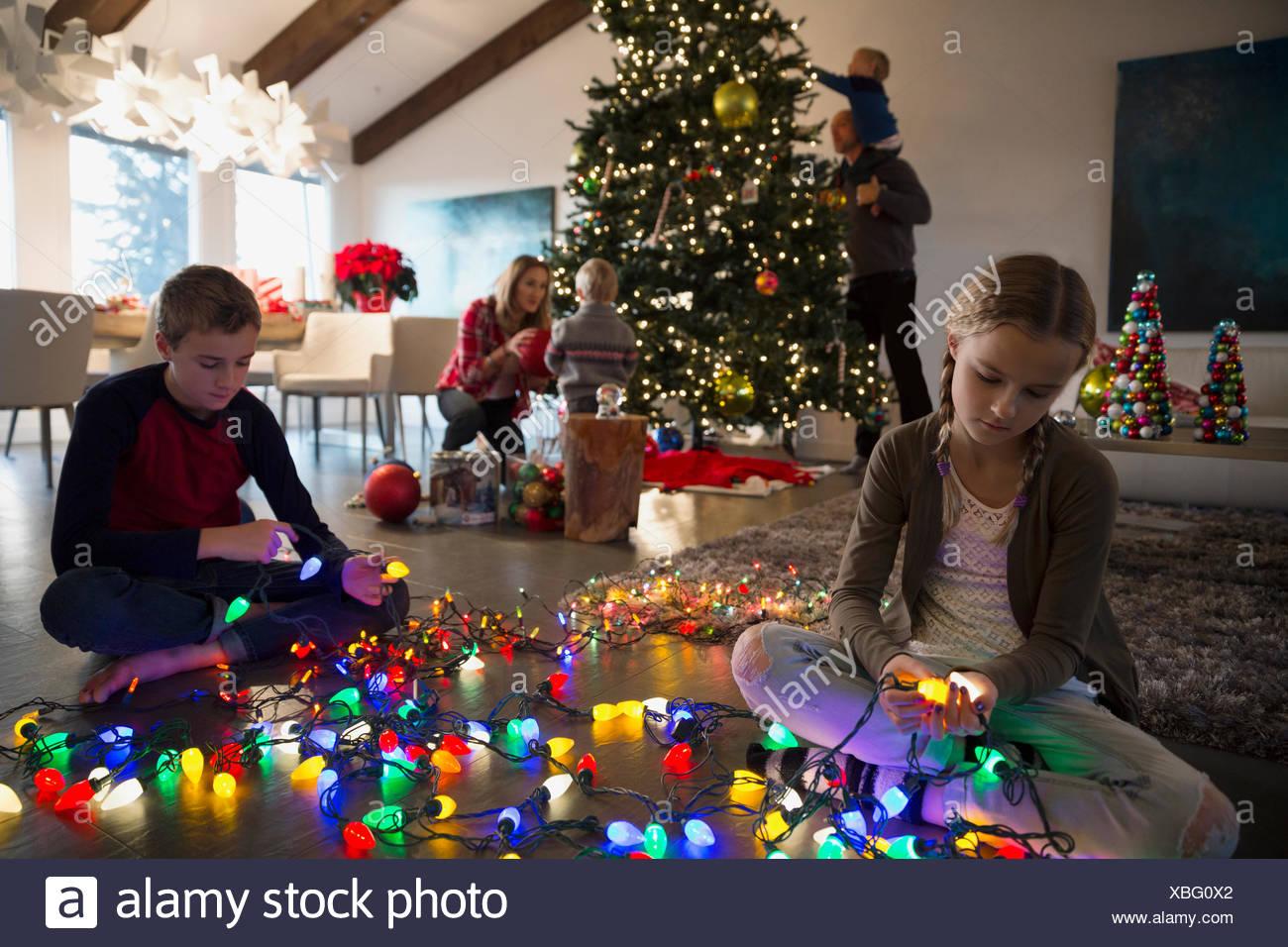 Fratello e Sorella untangling albero di Natale Luci di stringa Immagini Stock