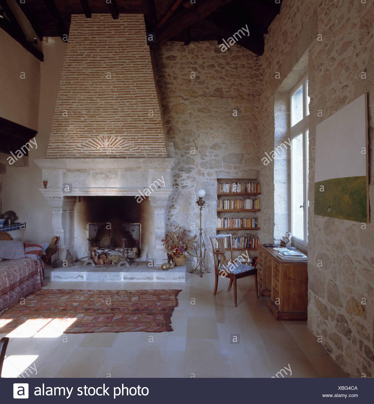 Grande camino in pietra nel paese soggiorno con pareti in pietra ...