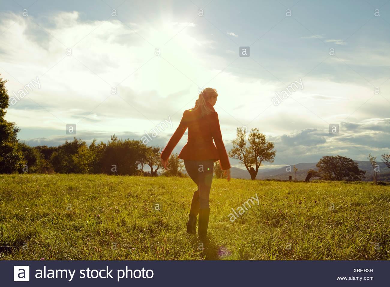 Giovane donna nel campo a piedi Immagini Stock