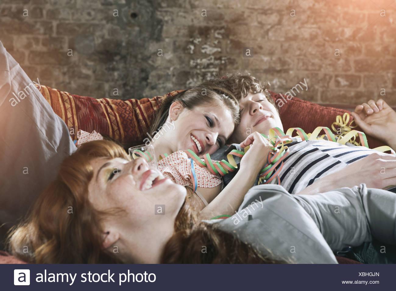 Germania, Berlino, Close up di giovani uomini e donne rilassante sul lettino, sorridente Immagini Stock