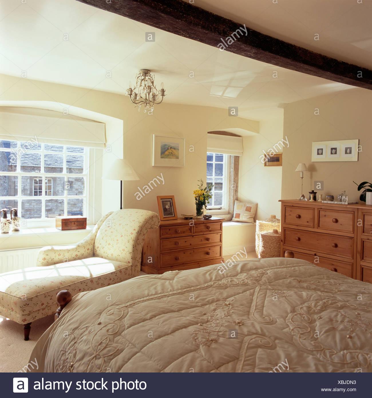 Panno beige sul letto nel paese di crema camera da letto con chaise ...
