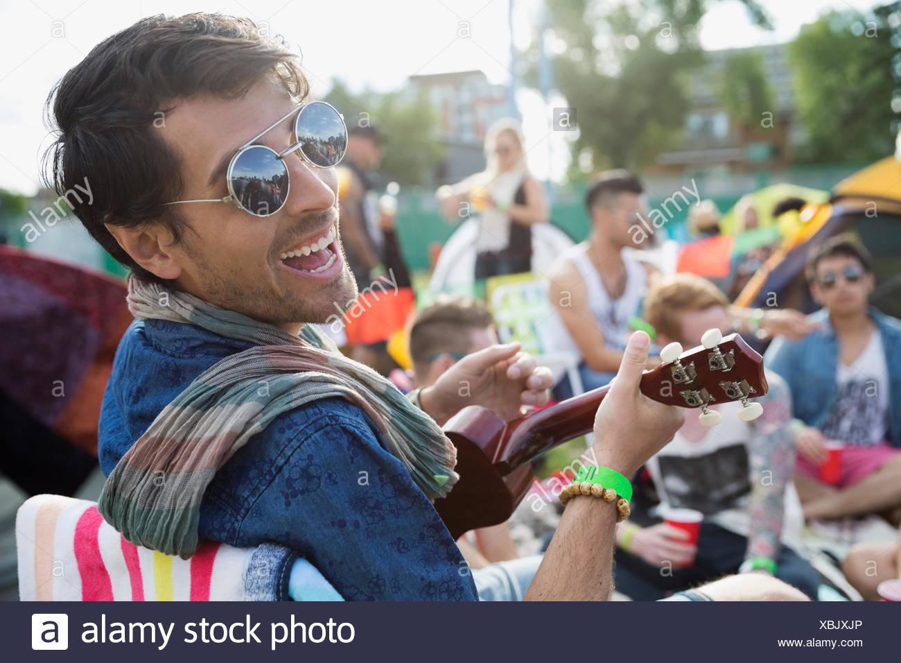 Ritratto di giovane entusiasta uomo giocando ukulele al festival musicale estivo Campeggio Immagini Stock