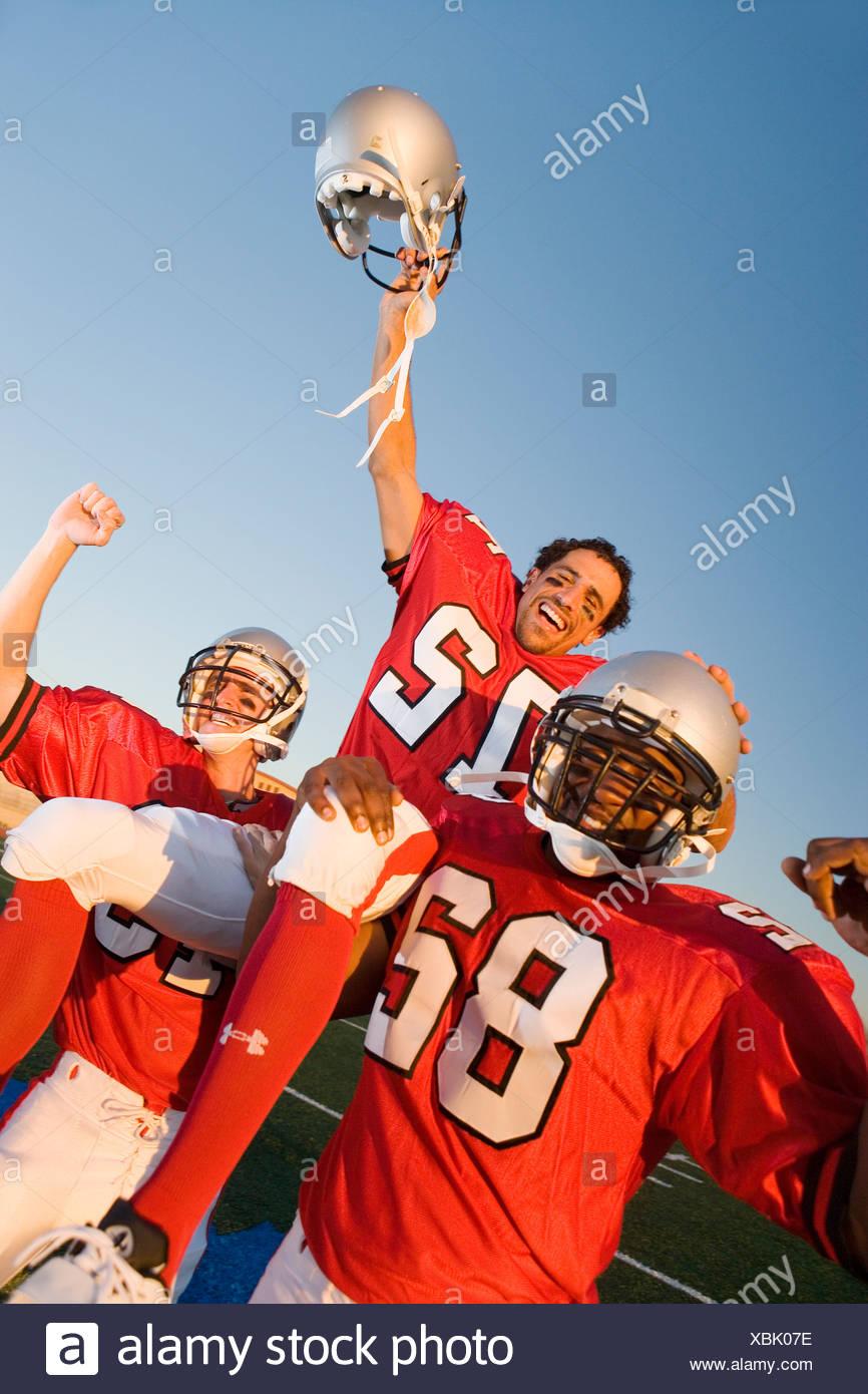 American football giocatori, in rosso il calcio strisce, celebrando la vittoria post partita, uomo portati sui compagni di squadra' spalle, ritratto Immagini Stock