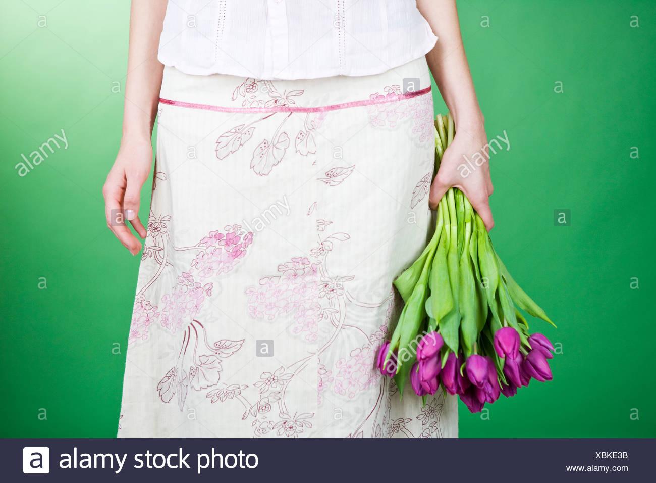 Donna che mantiene un mazzo di tulipani viola Immagini Stock