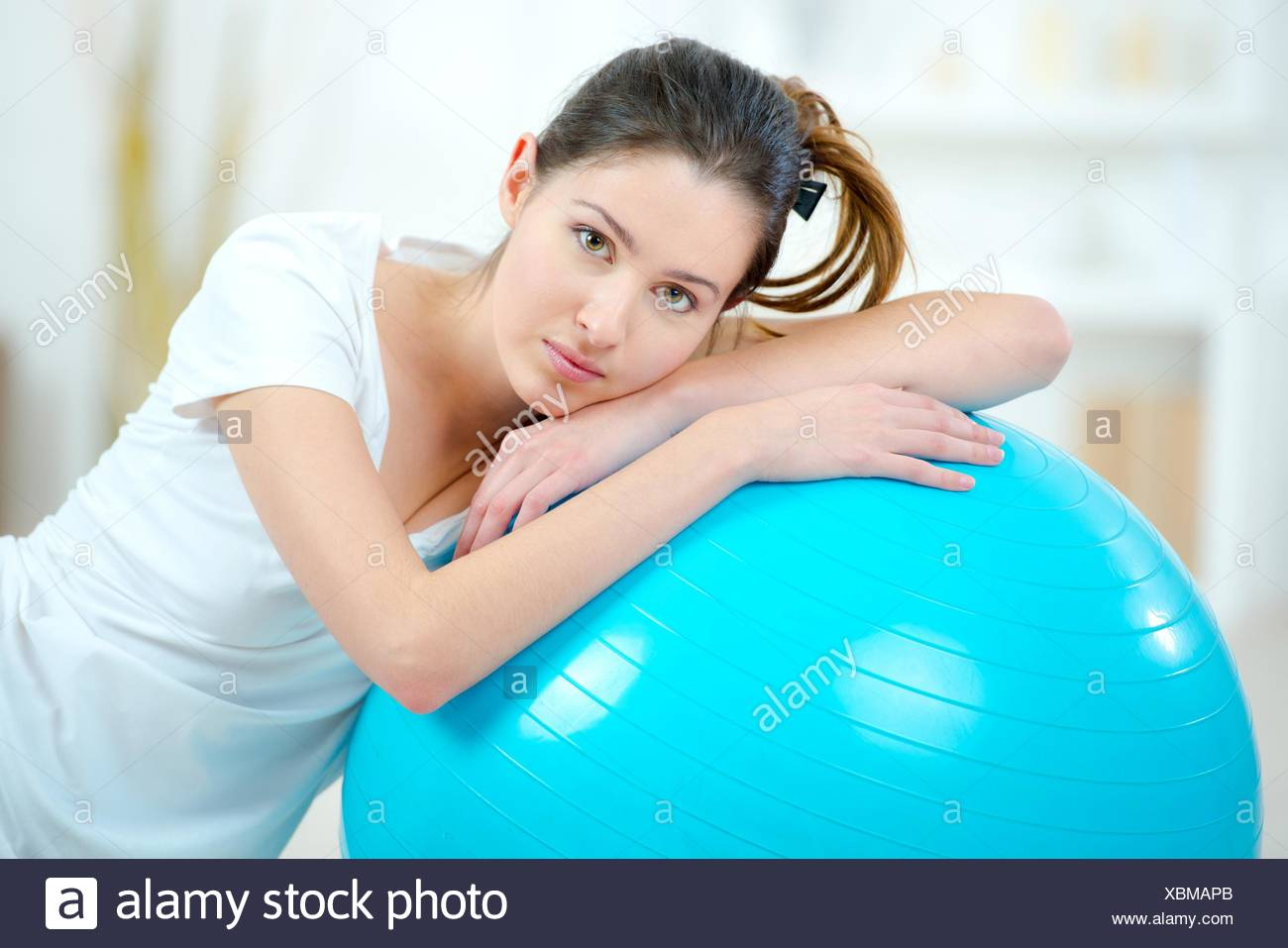 Ragazza appoggiata sulla sfera di aerobica Foto Stock