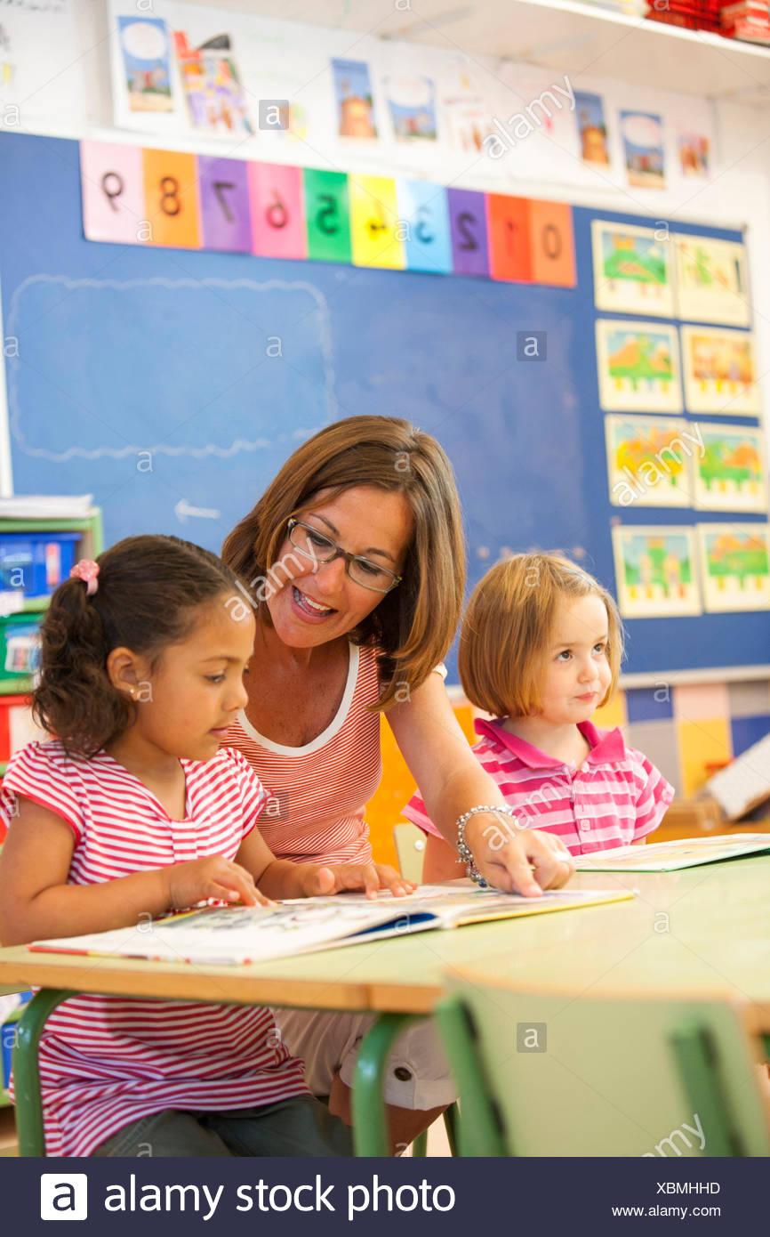 Le ragazze di età prescolare e insegnante storybook lettura in aula Immagini Stock