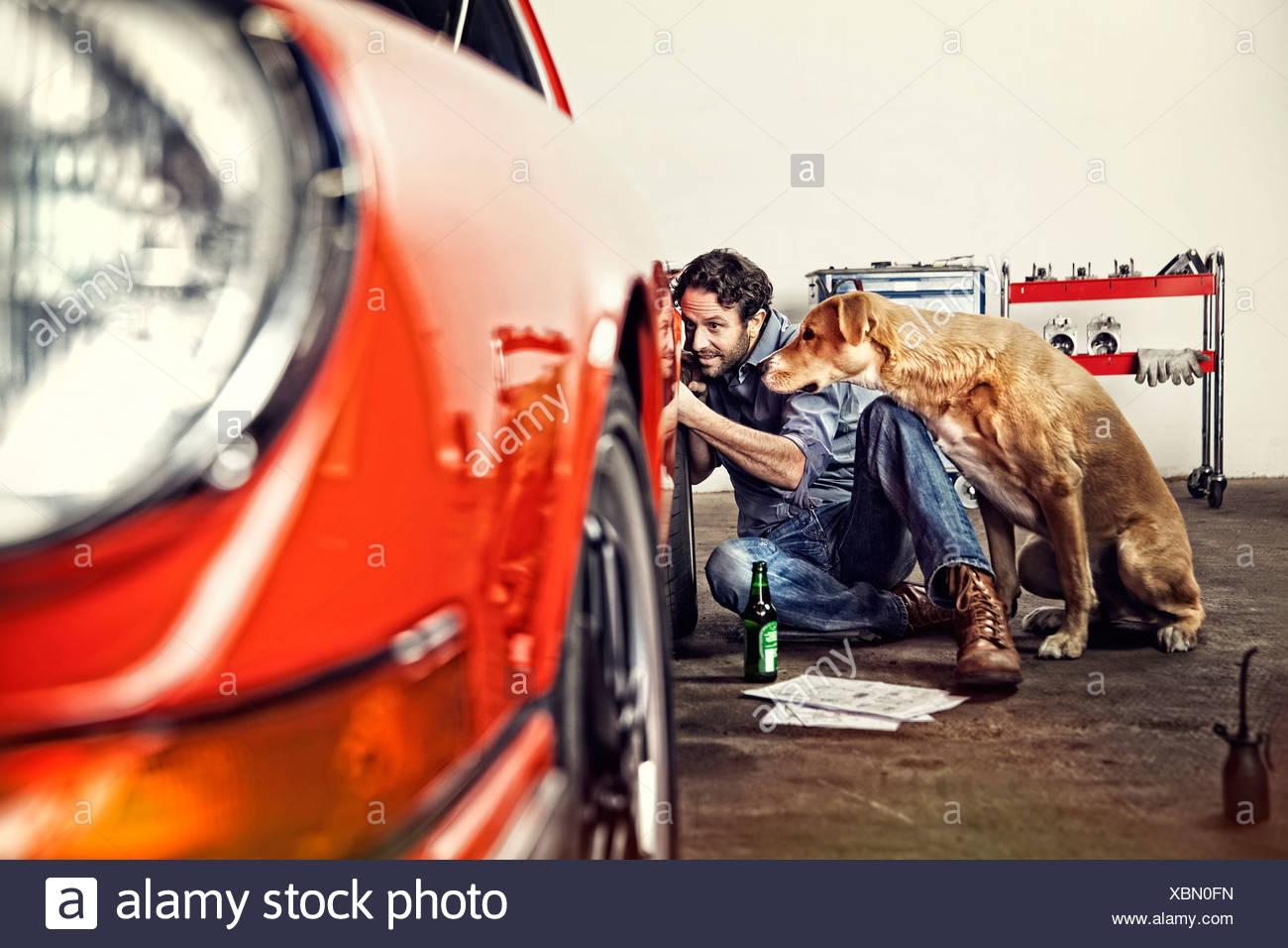 Uomo che ripara la sua auto d'epoca Immagini Stock