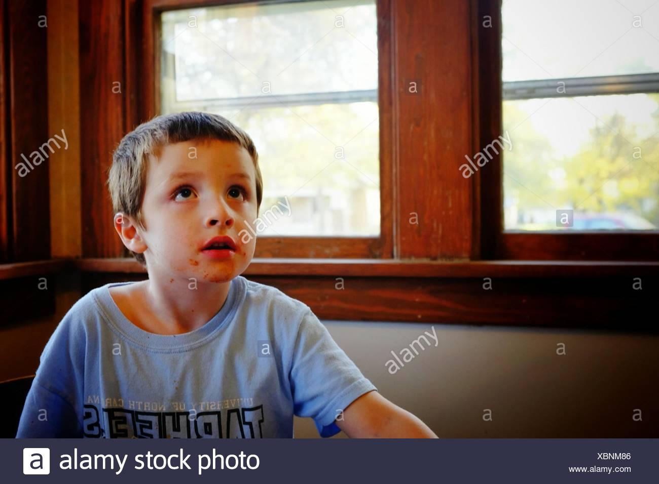 Carino Ragazzo che guarda verso l'alto dopo il pasto a casa Immagini Stock