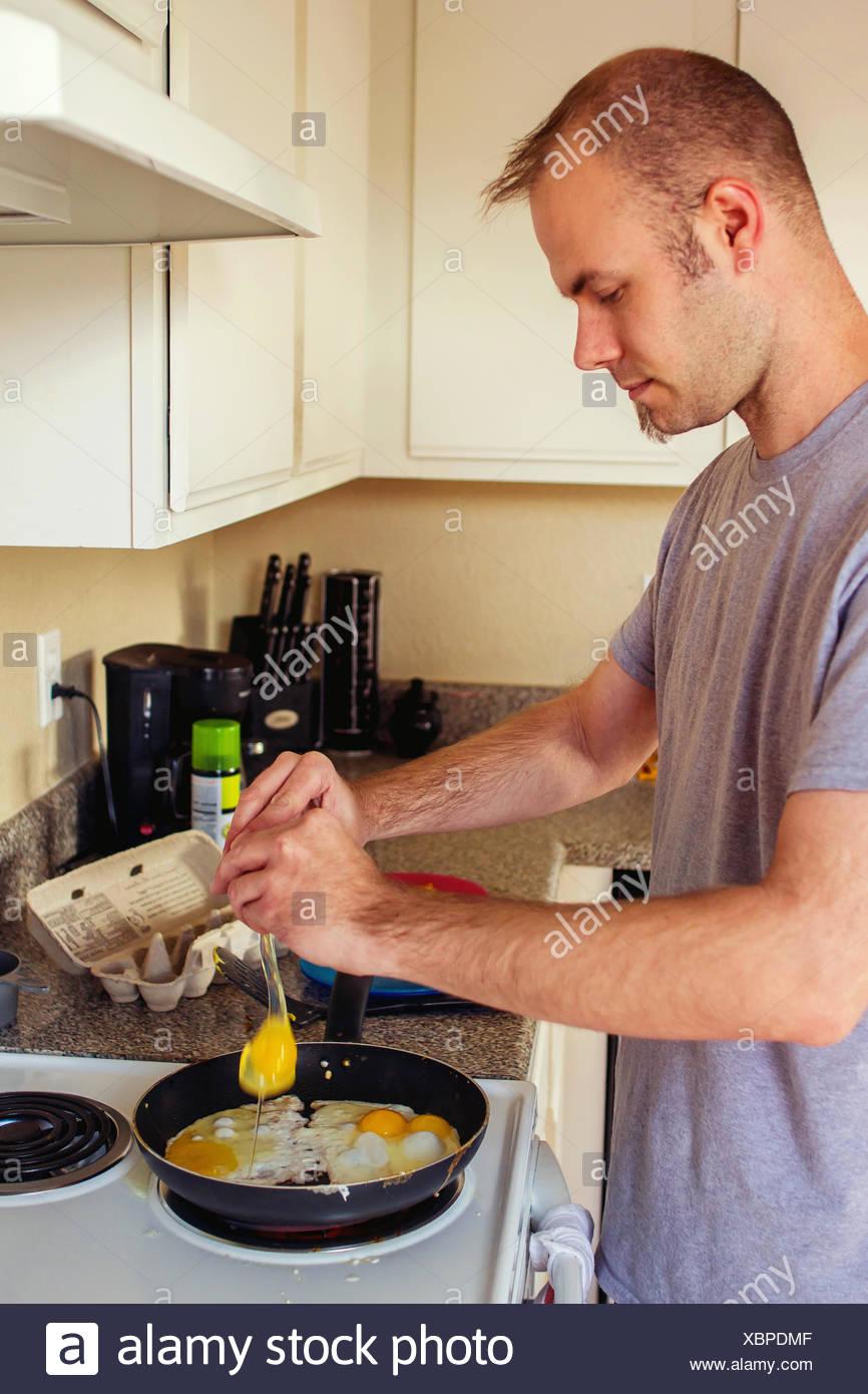 L'uomo cucinare uova fritte per la prima colazione Immagini Stock