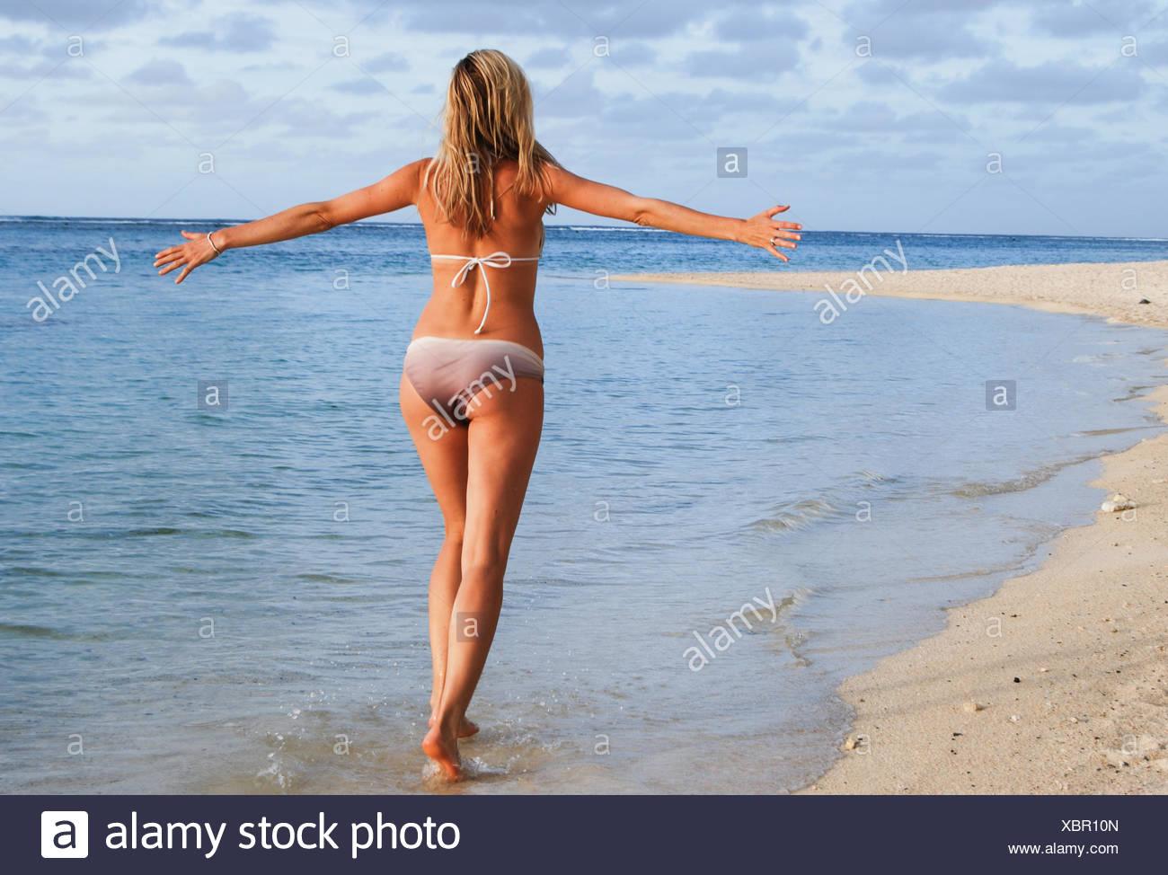 Vista posteriore della Donna che cammina sulla spiaggia con le braccia aperte Immagini Stock
