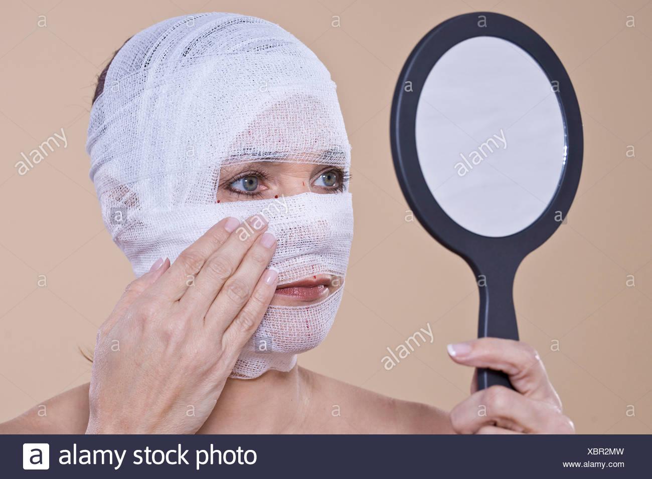 Donna controllando il suo volto benda con un specchio a mano Immagini Stock